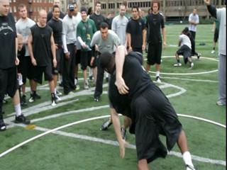 Portland State football coach Nigel Burton runs Bull in the Ring drill