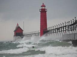 Surfers battle waves near Grand Haven pier during windstorm