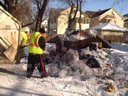City workers clean up trash behind East Side apartment buildng